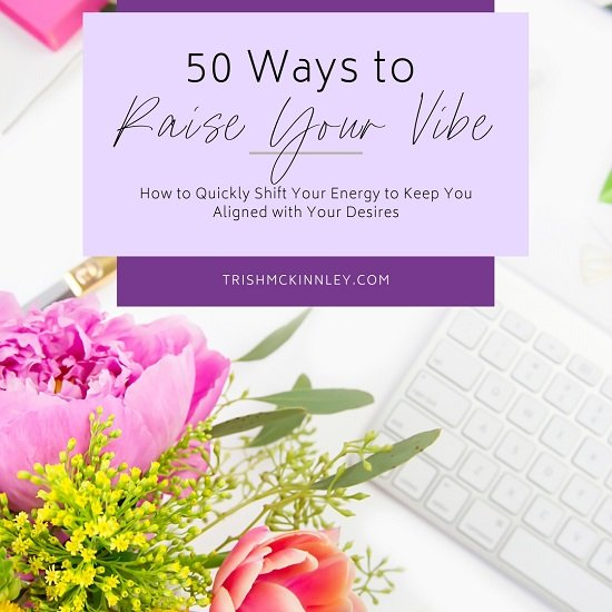 Table of flowers and laptop with title overlaying: ' 50 ways to raise your vibration - How to Quickly Shift Your Energy to Keep You Aligned with Your Desires'
