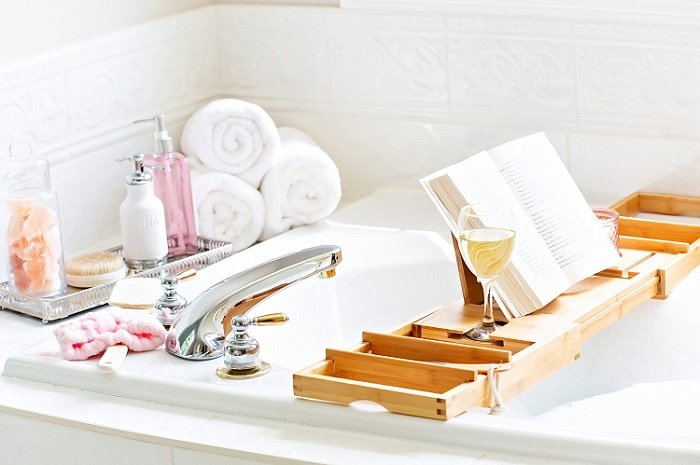 End of bath tub with book, wine and toileteries