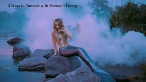 Connect with Mermaid Energy Image of mermaid sitting on a big rock be the ocean.