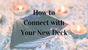 How to connect with your tarot deck on text with background showing a deck of tarot or oracle cards and candles.